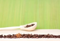 Coffee beans on wooden table with wooden spoon Royalty Free Stock Images