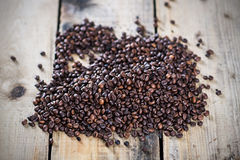 Coffee beans on wooden texture. Bunch of coffee beans on wooden floor Royalty Free Stock Photography