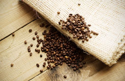 Coffee beans on wooden texture. Bunch of coffee beans on wooden floor and on coffee bag royalty free stock photos