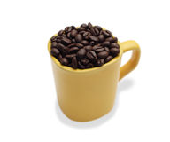 Coffee beans in a yellow ceramic mug.  isolated white backgr Stock Image