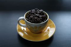 Cup of coffee with beans. Coffee beans in a yellow cup of coffee, black background, copyspace royalty free stock image