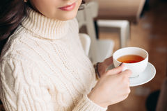 Coffee. Beautiful Girl Drinking Tea or Coffee. Cup of Hot Beverage. Brunette in a cafe drinking tea, eating sweets Stock Image