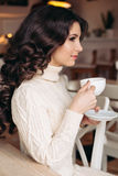 Coffee. Beautiful Girl Drinking Tea or Coffee. Cup of Hot Beverage. Brunette in a cafe drinking tea, eating sweets Royalty Free Stock Photos