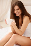 Coffee. Beautiful Girl Drinks Tea or Coffee Sitting on Bed Royalty Free Stock Photos