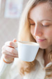 Coffee. Beautiful smiling girl holding in hand a cup of coffee Stock Image