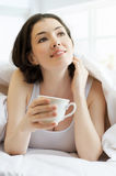 Coffee in bed. The girl enjoying her coffee in bed Royalty Free Stock Photography