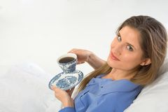 Coffee in bed. Drinking coffee in the bed female looks up Stock Images