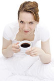 Coffee in bed. Young girl drinking coffee in bed Stock Photo