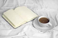 Coffee in bed. A cup of coffee and a book in top of a white bed Royalty Free Stock Photography