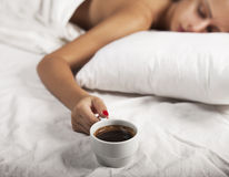 Coffee in Bed. A cup of coffee and young girl in a bed Stock Image