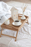 Coffee in bed. Wooden tray with coffee and interior decor on the bed with white linen Royalty Free Stock Photo