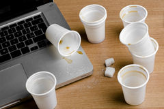 Coffee being dropped on laptop Royalty Free Stock Photos
