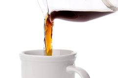Coffee being poured into a coffee cup on white Royalty Free Stock Photos