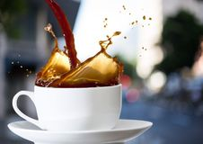 Coffee being poured into white cup against blurry street. Digital composite of Coffee being poured into white cup against blurry street Stock Image