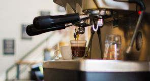 Coffee is being prepared by the machine in order to serve to a customer. stock images