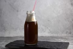 Coffee beverage in a glass bottle. On a black stone plate Royalty Free Stock Image