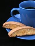 Coffee & Biscotti Closeup (on black). Black coffee in a bright blue cup with biscotti. Closeup with black background stock photos