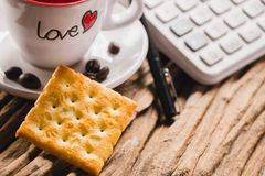 Coffee. A biscuit  and  a lovely cup of coffee   with some coffee beans , a pen and a calculator on the brown wood table for background Stock Photos