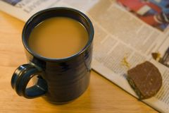 Coffee, biscuit & newspaper. A nice sit down and a cup of coffee or tea. Chocolate digestive and the paper too royalty free stock photography