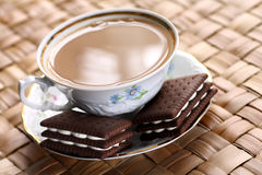 Coffee with biscuits. Close up of cup of hot coffee with milk and chocolate biscuits Royalty Free Stock Photography