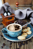 Coffee and biscuits. Blue old cup of black coffee, biscuits, coffee beans and linen cloth on the old wooden table Royalty Free Stock Photos