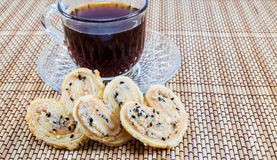 Coffee And Biscuits. Cup of coffee with crispy heart biscuits Royalty Free Stock Images