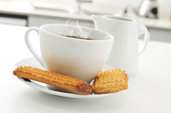 Coffee and biscuits on the kitchen table. A cup of coffee and some biscuits on the kitchen table Stock Image