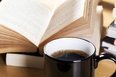 Coffee in black cup and open book pile Stock Photo