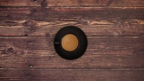 Cup of coffee on wooden background - stop motion. Coffee in Black cup on wooden background. Stop motion animation video stock video footage