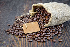 Coffee black grain with tag in bag on board Stock Images