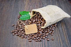 Coffee black grain with tag and leaf in bag on board Stock Photography