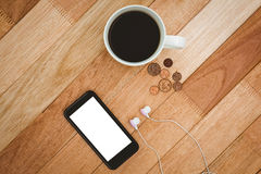 Coffee and black smartphone with white headphones Stock Photography