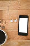 Coffee and black smartphone with white headphones Royalty Free Stock Photo