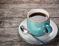 Coffee. A blue coffee cup full of black coffee with a spoon on a rustic wood background stock photo