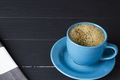 Coffee in blue cup with matching dish on black wooden background royalty free stock image