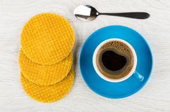 Coffee in blue cup on saucer, spoon, waffles with stuffed. On wooden table. Top view Stock Photo