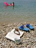 Coffee, book,  beach. Coffee, open book, sun glasses and girl on matrass enjoy at summer vacation at Adriatic sea  - spending holidays (Croatia, Dalmatia) Stock Photography