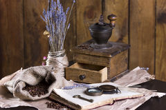 Coffee, book and coffee grinder. Old coffee grinder and a book lying on the crumpled paper. Coffee beans are scattered out of the bag. Dry lavender in a vase, a Stock Images