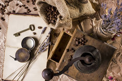 Coffee, book and coffee grinder. Old coffee grinder and a book lying on the crumpled paper. Coffee beans are scattered out of the bag. Dry lavender in a vase, a Royalty Free Stock Photos