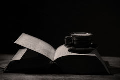 Coffee and a book. Drinking coffee and reading in the night, low light Royalty Free Stock Image