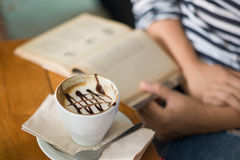 Coffee and book. A picture of a woman reading while drinking coffee royalty free stock photo