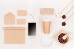 Coffee branding identity mockup - brown paper cup with blank phone, label, card, notebook, mortar with coffee beans on white wood. Board, top view stock image