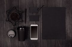 Coffee branding identity mockup in light modern style - black paper cup, blank phone, card, label, cap, statuette with coffee bean. S on black wood board royalty free stock image