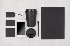 Coffee branding identity mockup in light modern style - black paper cup, blank screen phone, card, label, paper, cap on white wood. Board, top view stock images