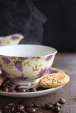 Coffee breack. Coffee beans and coffee cup with biscuits ans steam Royalty Free Stock Photography