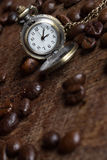 Coffee breack. Coffee beans and vintage clock Stock Photo