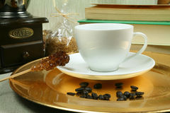 Coffee break. White cup on the golden plate, manual mill and books Royalty Free Stock Images