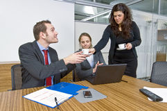 Coffee break. A small business team taking a short break when a businesswoman hands out cups of coffee to her colleagues during a meeting stock image