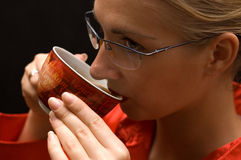 Coffee break. Blond girl with glasses drinks hot coffee Stock Photos