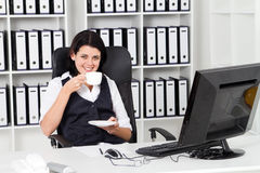 Coffee break. A happy young businesswoman having a coffee break at her office desk stock photos